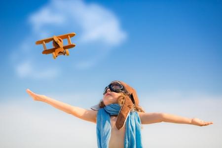 Счастливый ребенок, играя с игрушкой самолета на фоне голубого неба летом