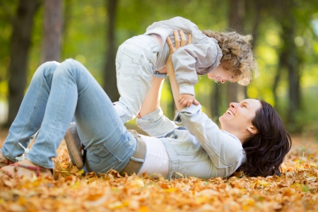 Happy family having fun outdoors in autumn park against blurred leaves background Stock Photo - 20384491