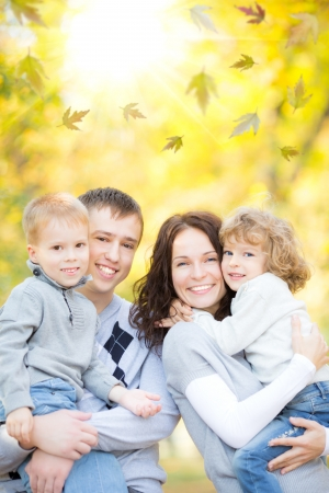 family outdoors: Happy family having fun outdoors in autumn park against blurred leaves background