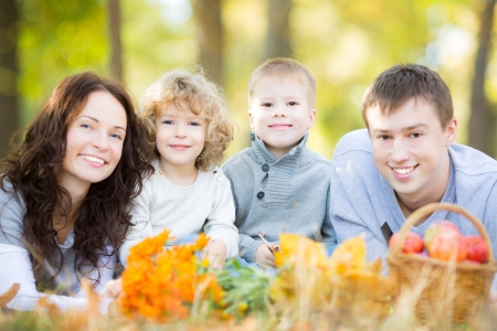family park: Happy family having picnic outdoors in autumn park against blurred leaves background Stock Photo