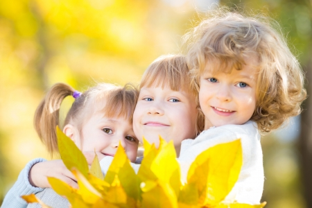 Happy children with maple leaves in autumn park photo