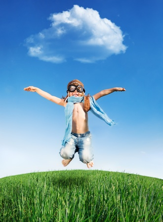 blue summer sky: Happy kid dressed as a pilot jumping in green field against blue sky  Summer vacation concept Stock Photo