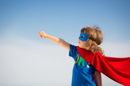 super human: Chico super h�roe contra el fondo del cielo azul Foto de archivo