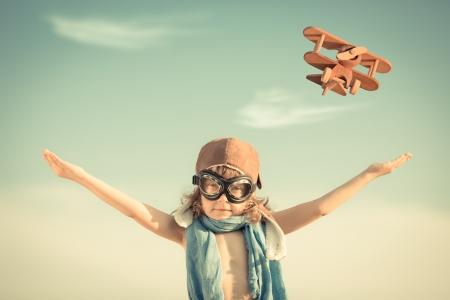 Gelukkige jongen speelt met speelgoed vliegtuig tegen blauwe zomer hemel achtergrond
