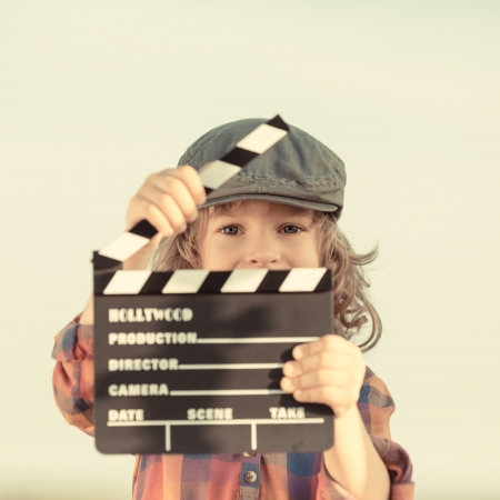 Kid holding clapper board in hands photo