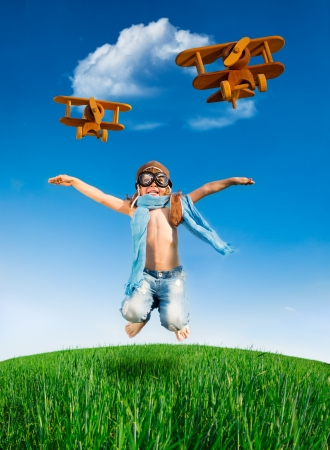 toy plane: Happy kid dressed as a pilot jumping in green field against blue sky Stock Photo