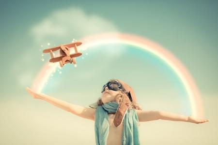 Gelukkige jongen speelt met speelgoed vliegtuig tegen de zomer hemel achtergrond