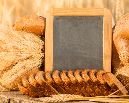 Bread and wheat on the wooden table in autumn field  Blackboard with copyspace photo
