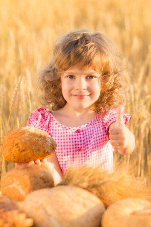 Happy child holding bread against yellow autumn wheat field photo