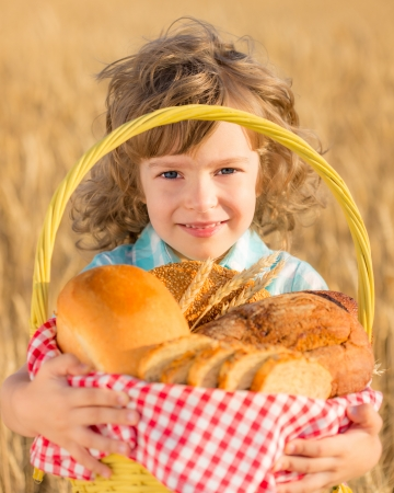 bake sale: Happy child holding basket with bread in yellow autumn wheat field