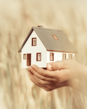 House in children s hands against autumn yellow background  Real estate concept Reklamní fotografie