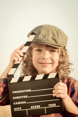 Kid holding clapper board in hands  Cinema concept  Retro style Stock Photo - 21384748