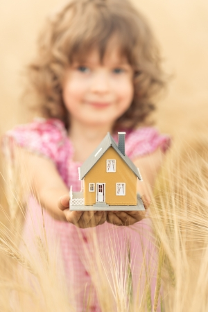 Happy child holding house in hands against autumn yellow background  Real estate concept photo