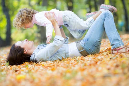 Happy family having fun outdoors in autumn park against blurred leaves background photo