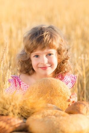 Happy child holding bread in hands against yellow autumn wheat field photo