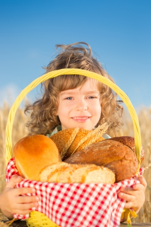 Happy child holding basket with bread in yellow autumn wheat field against blue sky background photo