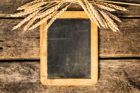 Autumn wheat on old wood blackboard photo