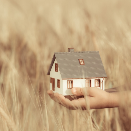 House in children s hands against autumn yellow background  Real estate concept photo