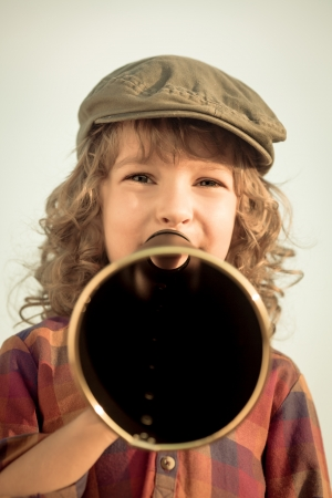 Kid shouting through vintage megaphone  Communication concept  Retro style photo
