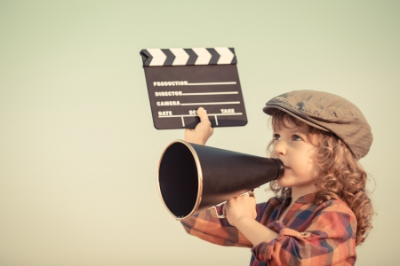 movies: Kid holding clapper board and shouting through vintage megaphone  Cinema concept  Retro style