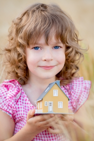 Child holding house in hands against autumn yellow background  Real estate concept Stock Photo - 21503129