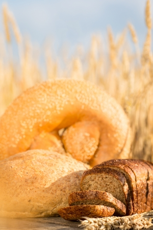 Homemade bread and wheat on the wooden table in autumn field photo
