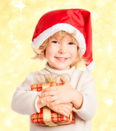 Happy baby holding gift box against Christmas ligths blurred background photo