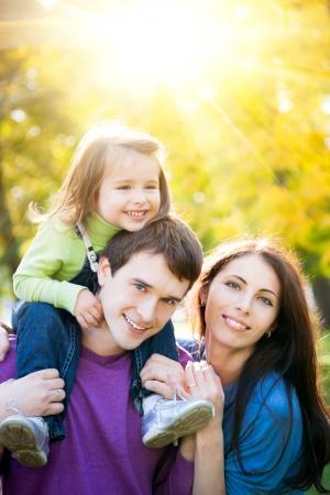 outdoor: Familia feliz que se divierte al aire libre en el parque de otoño sobre fondo soleado de oro Foto de archivo