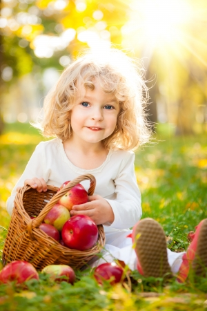 Happy child with basket of red apples in autumn park against golden sunny background photo