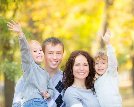 candid: Happy family having fun outdoors in autumn park against blurred leaves background