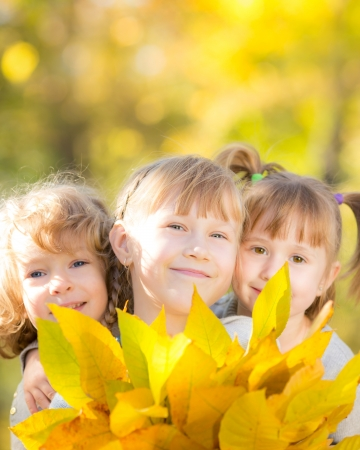 fall fun: Happy children with maple leaves in autumn park
