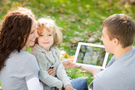 person outside: Happy family using tablet PC outdoors in autumn park