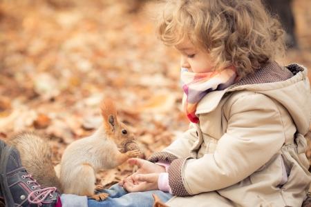 Happy child feeds a little squirrel in autumn park