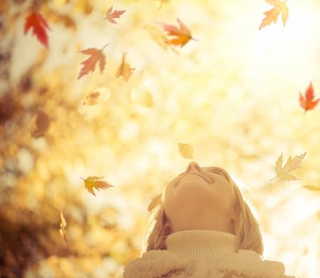 felicidad: Niño feliz con las hojas de arce en el Parque de otoño contra hojas amarillas de fondo borroso concepto de la libertad Foto de archivo