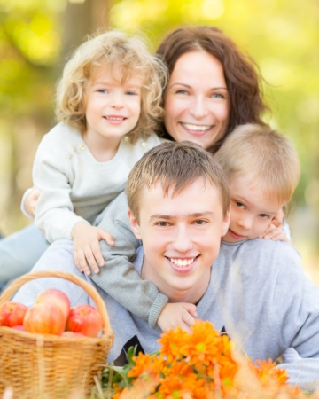 Happy family having picnic outdoors in autumn park against blurred leaves background Stock Photo - 21863631