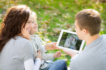 Happy family using tablet PC outdoors in autumn park photo