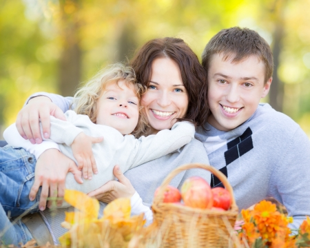 Happy family having picnic outdoors in autumn park against blurred leaves background photo