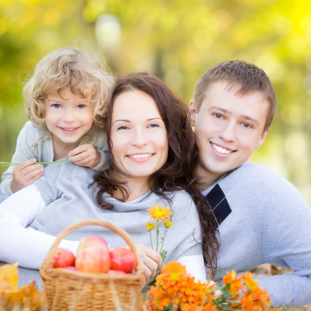 Happy family having picnic outdoors in autumn park against blurred leaves background Stock Photo