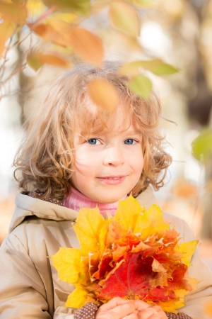 Happy child with maple leaf in autumn park against yellow blurred leaves background photo