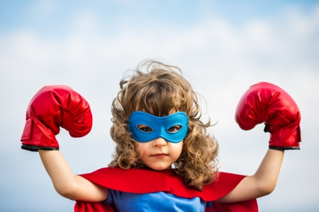 Superhero kid wearing boxing gloves against blue sky  Stok Fotoğraf