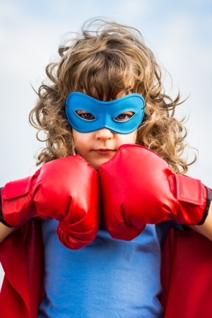 Superhero kid wearing boxing gloves against blue sky  Stock Photo