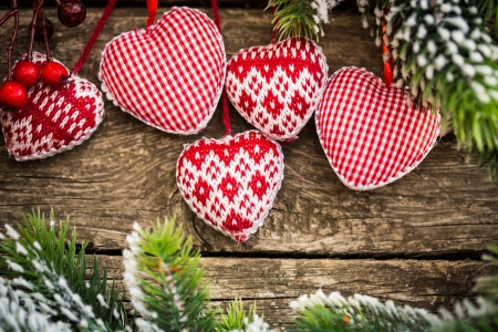 Christmas tree decorations hanging on branch against wooden. Winter holidays concept Фото со стока
