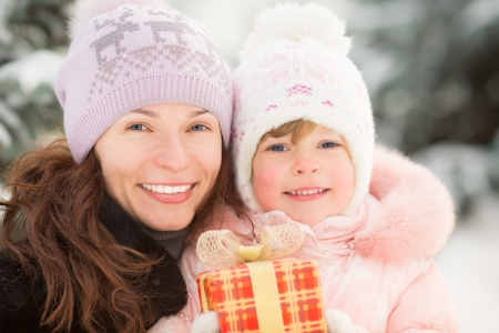 Happy family holding gift box in winter outdoors. Christmas holidays concept Stock Photo - 22428923