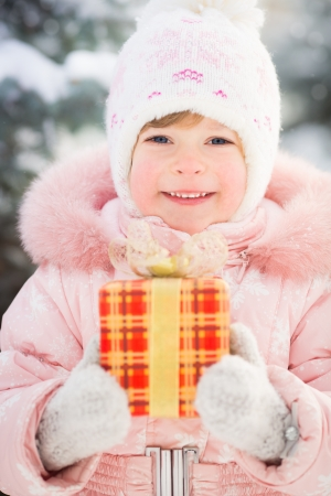 Happy family holding gift box in winter outdoors photo