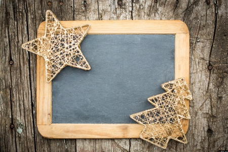 Gold Christmas tree decorations on vintage wooden blackboard  Winter holidays concept  Copy space for your text photo