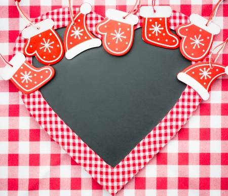 Card blank in heart shape with Christmas tree decorations on red gingham tablecloth  Winter holidays concept  Copy space for your text photo
