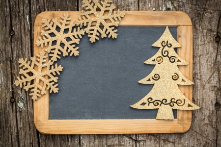 feliz: Gold Christmas tree decorations on vintage wooden blackboard with copy space  Xmas holidays card