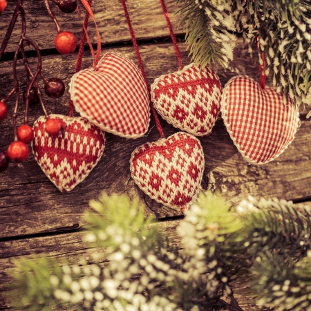 Christmas tree decorations hanging on branch against wooden background. Winter holidays concept. Shallow depth of fields photo