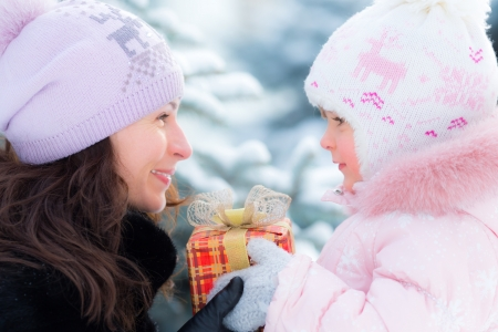Happy family holding gift box in winter outdoors. Christmas holidays concept photo