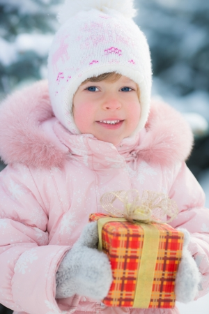 Happy child holding gift box in winter outdoors  Christmas holidays concept Stock Photo - 22579159